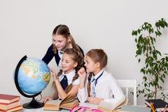 在教室学习行星地球的地理地球三个女孩 免版税库存照片