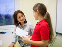 在教室教育有笔记本和老师的女孩 库存图片