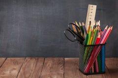 在教室桌上的学校和办公用品 免版税库存照片