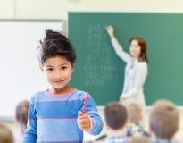 在教室背景的愉快的矮小的学校女孩 免版税图库摄影