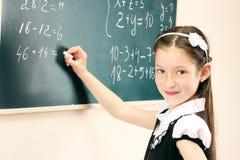 在教室董事会的女孩文字 免版税库存照片