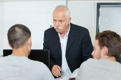 在教训期间的资深老师在教室 库存照片