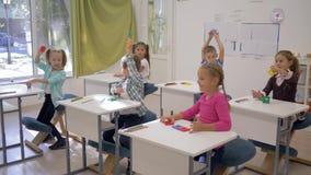 在教训期间,幼儿教育,聪明的愉快的孩子在手中提起几何形状 股票录像