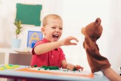 在教训期间的小男孩与他的语言矫治者 免版税库存图片