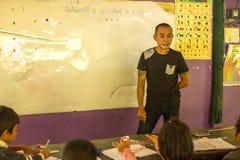 在教训的Ticher在项目柬埔语的学校在被剥夺的区域哄骗关心帮助被剥夺的孩子与教育 免版税库存图片