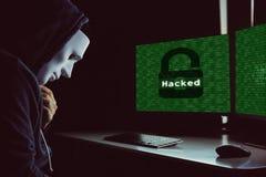 在敞篷下的被掩没的黑客使用计算机乱砍入系统和设法做计算机犯罪 库存照片