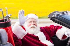在敞篷车的圣诞老人有高尔夫俱乐部的 免版税图库摄影