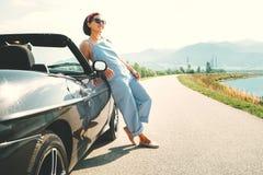 在敞蓬车汽车附近的少妇独奏旅客逗留在美丽如画 免版税库存图片
