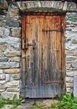 在散石墙壁的老木门有生锈的铰链和挂锁的 库存照片