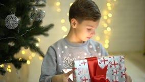 在敬畏惊奇的愉快的激动的小男孩开头圣诞节礼物礼物盒坐近在新年树下 影视素材