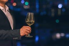 在敬酒一杯白酒的屋顶酒吧的商人佩带的水军蓝色颜色衣服立场有城市黑暗的背景  免版税库存照片