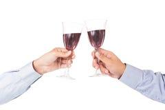 在敬酒在水晶玻璃的长的袖子衬衣的手红葡萄酒 免版税库存图片