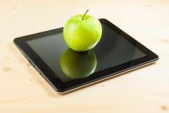 在数字式片剂个人计算机的绿色苹果在木桌上 图库摄影