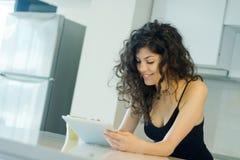 在数字式片剂的微笑的妇女读书 免版税库存图片