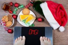 在数字式等级的女性脚与标志omg!围拢由圣诞节装饰、瓶、杯酒精和甜点 免版税库存图片