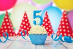 在数字形状的生日蜡烛在杯形蛋糕的 库存图片