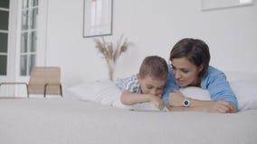在数字片剂的愉快的年轻母亲陈列动画片对她的在去前的小孩儿子睡 愉快的母亲陈列 股票录像