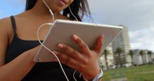 在数字片剂的残疾妇女听的音乐特写镜头在公园4k 股票视频