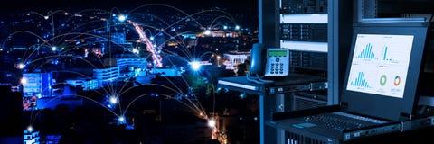 在数据中心和连通性的管理和监视显示器排行在夜城市背景 免版税库存图片