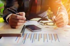 在数据纸和使用智能手机的商人分析在 免版税库存图片
