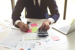 在数据纸的商人分析使用计算器和膝上型计算机 免版税库存照片