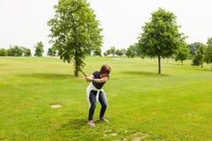 在敲的妇女在高尔夫球场期间 免版税库存照片