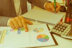 在文书工作帐户的特写镜头笔与人保存数据的用途计算机在背景中 会计科目背景计算器概念现有量查出在白色 免版税库存照片