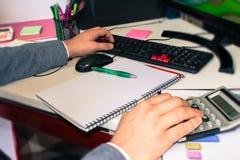 在文书工作帐户的特写镜头笔与人保存数据的用途计算机在背景中 会计科目背景计算器概念现有量查出在白色 图库摄影