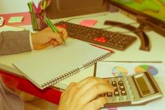 在文书工作帐户的特写镜头笔与人保存数据的用途计算机在背景中 会计科目背景计算器概念现有量查出在白色 库存图片