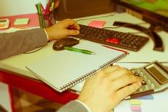 在文书工作帐户的特写镜头笔与人保存数据的用途计算机在背景中 会计科目背景计算器概念现有量查出在白色 免版税图库摄影