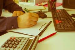 在文书工作帐户的特写镜头笔与人保存数据的用途计算机在背景中 会计科目背景计算器概念现有量查出在白色 免版税库存图片