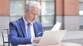 在文件和膝上型计算机的老商人工作,室外 股票视频