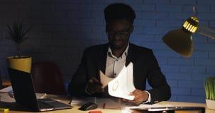 在文件错误地混淆的被注重的商人运作在书桌在夜办公室 工作狂,最后期限概念 股票录像