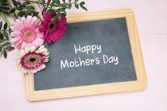 在文字黑板的三朵大丁草花,发短信给愉快的母亲 免版税库存照片