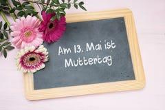 在文字黑板的三朵大丁草花,德国文本上午13 库存图片