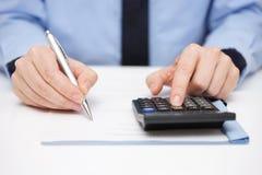在文件和使用计算器的商人文字在同样 免版税库存图片