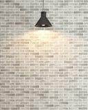 在斑点光翻译下的白色砖墙装饰 免版税库存图片