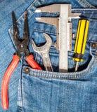 在斜纹布口袋的工具箱 免版税库存照片