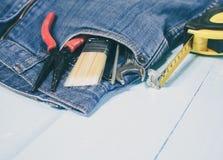 在斜纹布口袋的工具箱 库存图片