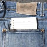 在斜纹布口袋的笔记本纸 免版税库存图片