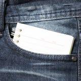 在斜纹布口袋的笔记本纸 图库摄影
