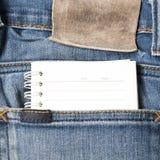 在斜纹布口袋的笔记本纸 库存图片