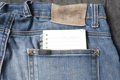 在斜纹布口袋的笔记本纸 库存照片