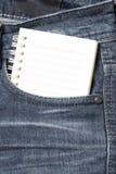 在斜纹布口袋的笔记本纸 免版税库存照片