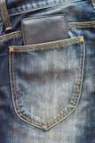 在斜纹布口袋的黑钱包 免版税库存照片