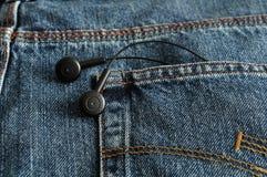 在斜纹布的一个口袋的耳机 库存照片