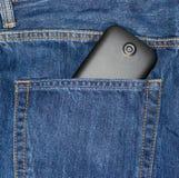 在斜纹布的巧妙的电话装在口袋里 库存照片