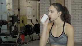在断裂期间的女运动员喝从玻璃的水在健身房 影视素材
