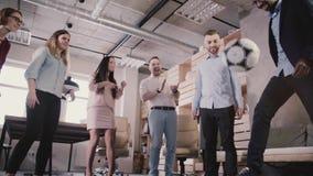 在断裂期间,不同种族的办公室同事使用与橄榄球 愉快的雇员举行偶然体育活动慢动作 股票录像