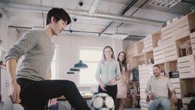 在断裂期间,亚裔人使用与橄榄球在办公室 愉快的朋友在圈子站立,举行体育活动慢动作 影视素材